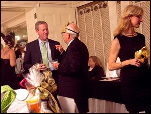 Jim Hoffman, left, talks with John Davies, center, in the silent auction room Saturday evening during the Blue Moon Ball at the Toledo Club.