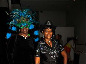 Dressed as a peacock and a cowgirl, Rhonda Hill, right, and Cassandra Williams pose during the Bone Bash to benefit the Arthritis Foundation.