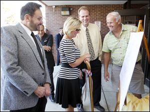Dr. Michael Granata, dental director of the Monroe County Health Department, left, and Tracy Cedar of the Michigan Community Dental Clinics, look at the site plan for the future dental clinic for low-income persons with county Commissioners Jerry Oley, second from right, and Dave Hoffman.