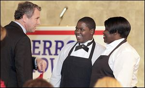 Sen. Sherrod Brown, left, introduces himself to dinner servers La'Mai Moore, center, and her mother, Melody Moore, both of Toledo, at the Lucas County Democratic Party's annual fall dinner.