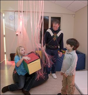 Sophia Rogers, 9, her brother Jack, 6, and their grandfather, Don Rogers of Mentor, Ohio, check out the Special Kids Therapy Playroom. The box Sophia holds controls the color of the light in the room, including the color of the fiber-optic cables hanging around her; the room has a reddish cast because the box's red side is on top.