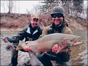 Kelly Gilmore of Mentor, Ohio, left, and Will Waldrip fo Austin, Texas, with a trophy steelhead caught on the Rockey River.