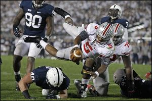 Ohio State quarterback Braxton Miller dives over Penn State linebacker Glenn Carson (40) for a third-quarter touchdown.