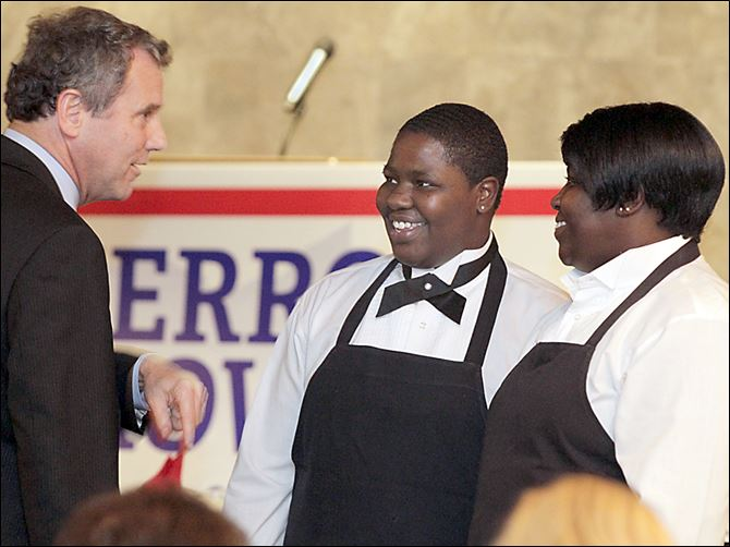 Sen. Sherrod Brown, left, introduces himself Sen. Sherrod Brown, left, introduces himself to dinner servers La'Mai Moore, center, and her mother, Melody Moore, both of Toledo, at the Lucas County Democratic Party's annual fall dinner.