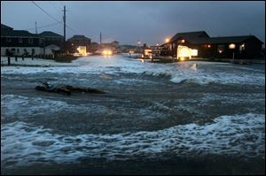 Ocean water rolls over state highway NC 12 in Buxton, N.C., on Hatteras Island at dawn as Hurricane Sandy works its way north, battering the East Coast.