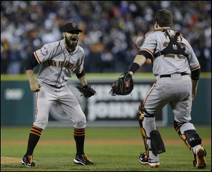 San Francisco Giants' Sergio Romo and catcher Buster Posey celebrate after the Giants defeated the Detroit Tigers, 4-3, in Game 4 of baseball's World Series Sunday.