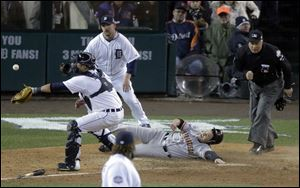 San Francisco Giants second baseman Ryan Theriot slides safely to score a run past Detroit Tigers catcher Gerald Laird during the 10th inning of Game 4 of baseball's World Series against the Detroit Tigers Sunday.