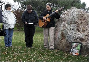 Gaby Davis, left, Michelle Clossick, and Lisa Binkowski gather around the Violence Against Women Memorial Rock at the Sanger Branch Library to share a moment of silence for Amber Jones, 26, of Lake Township and her son, Jorge Duran III, 3, shown in framed photo, along with Lorie Miller of Sandusky, who died this month in alleged acts of domestic violence.