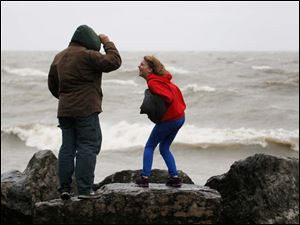 Alex Czerwinski and his daughter Alia, 12, of Port Clinton, stand on the rocks along the Lake Erie shoreline at Marblehead Lighthouse State Park in Marblehead Monday.
