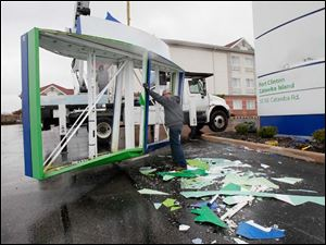 Steve Hanley, on truck, and Ben Nicholas, of Watkins Lighting in Berea, Ohio, remove a sign that was blown down at the Holiday Inn Express on Northeast Catawba Road east of  Port Clinton Monday.  The effects of Hurricane Sandy were being felt along the Lake Erie coastal area in Ottawa County.