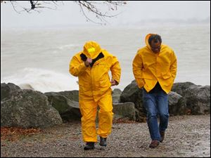 Alex Shartle of Dayton, left, and Keith Bell of Kent, walk along the Lake Erie shore at Marblehead Lighthouse State Park Monday.
