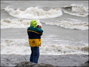 John Francis of Akron, Ohio, photographs the waves in Lake Erie at Marblehead Lighthouse State Park in Marblehead, Ohio, Monday.