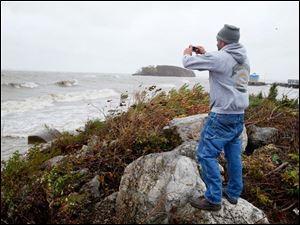 Mark Beard of Oak Harbor photographs the waves in Lake Erie at Catawba Island Monday.