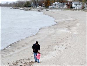 Rashid Solo, left, looks for shells with his daughter Brooklyn Solo, 2, of Utah, on the shoreline during heavy winds in Luna Pier Monday.