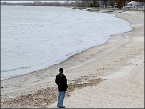 Rashid Solo of Utah looks out over the shoreline during heavy winds in Luna Pier Monday.