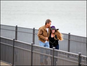 Randy Rozelle, left, clasps his daughter Brooke Rozelle, 16, both of Florida, while walking on the pier during heavy winds at the shore in Luna Pier Monday.