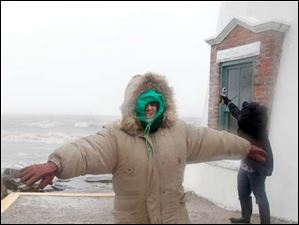 Sharon Cogle, Toledo, braces herself against the wind as Channel 13 ABC meteorologist Ross Ellet uses an anemometer to measure the wind speed at Marblehead Lighthouse State Park in Marblehead Tuesday.  Mrs. Cogle was having fun watching the storm with her husband Jess Cogle. Mr. Ellet said he was recording sustained wind speeds of 40-45 miles per hour with gusts to 55 miles per hour. Mr. Ellet also said he recorded a maximum speed of 79 miles per hour around day break.