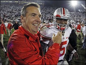 Ohio State head coach Urban Meyer, left, celebrates with Ohio State quarterback Braxton Miller (5) at the end of a 35-23 win over Penn State in an  NCAA college football game in State College, Pa.