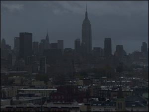 The Empire State Building and Midtown Manhattan are dark in this view from Jersey City, N.J., Tuesday morning after a powerful storm that started out as Hurricane Sandy made landfall on the East Coast.