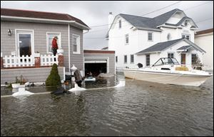 A boat floats in the driveway of a home in the aftermath of superstorm Sandy in Lindenhurst, N.Y.