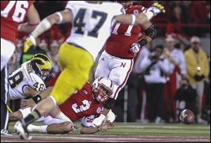 Nebraska quarterback Taylor Martinez fumbles the ball for a turnover after being tackled by Michigan's Desmond Morgan (48).