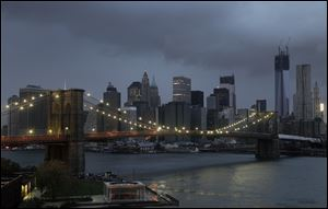 The lights on the Brooklyn Bridge stand in contrast to the lower Manhattan skyline which has lost its electrical supply after megastorm Sandy swept through New York.