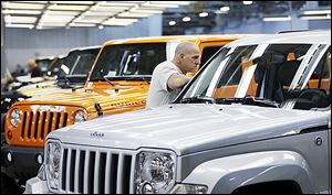 A worker looks over a Liberty at Chrysler's Toledo assembly complex this year.
