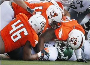 Bowling Green State University players Charlie Walker, 46, Gabe Martin, 11, and Paul Swan, 33, smother Eastern Michigan University player Bronson Hill, 30.