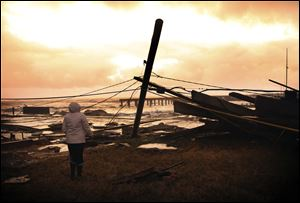 Kim Johnson looks over the destruction from superstorm Sandy near her seaside apartment in Atlantic City, N.J., today.