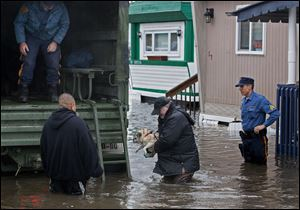 With the aid of New Jersey State police, a man walks with his dog to a National Guard vehicle after leaving his flooded home at the Metropolitan Trailer Park in Moonachie, N.J., Tuesday, in the wake of superstorm Sandy.