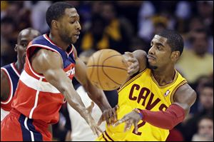 Cleveland Cavaliers' Kyrie Irving passes away from Washington Wizards' A.J. Price in the first quarter Tuesday, in Cleveland.