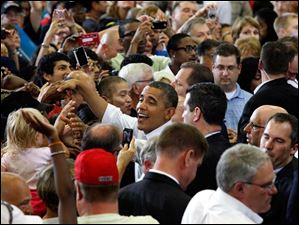 President Obama is surrounded by supporters as he leaves Scott High School after speaking on Sept. 3, 2012.