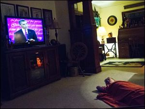 Sydnie Abke, 10, keeps an eye on the presidential debate while her parents, Marcy and Russ, watch at their home in Pemberville.