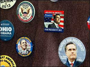 A collection of political buttons on display features Obama and Romney prominently in front of the display case at the in Elyria at the Elyria Public Library on Oct. 10, 2012.