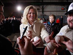 Ann Romney, wife of Republican presidential candidate Mitt Romney, signs baseballs during a campaign appearance at American Posts LLC in Toledo Feb. 29, 2012.
