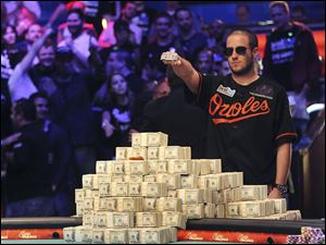 Greg Merson holds up his new bracelet after winning the World Series of Poker No-Limit Hold'em Main Event, today in Las Vegas.