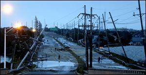 Downed power lines and a battered road is what superstorm Sandy left behind Tuesday as people walk off the flooded Seaside Heights island.