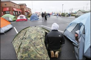 Scott West of Perrysburg, left, and Jamie Adams of Millbury, right, join others camping outside Wednesday at the Chick-Fil-A restaurant in Perrysburg Township.  The restaurant opens Thursday. The first 100 participants who comply with the official rules of a company grand opening promotion receive a grand prize of one Chick-fil-A meal per week for a year.