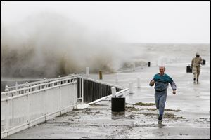 Bill Klaehn, Marblehead, outruns his son George Klaehn, 17, Tuesday after taking pictures of waves crashing over the dock at Lakeside, Ohio.