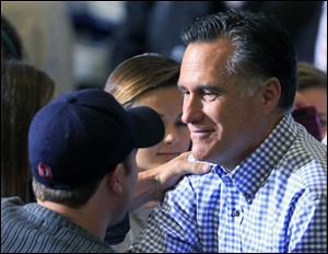 Republican presidential candidate Mitt Romney shakes hands with a supporter while collecting donations at a storm relief event, Tuesday at James S. Trent Arena in Kettering, Ohio.