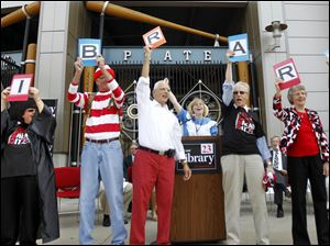 "Staff members of The Toledo-Lucas County Public Library hold up letters that spell ""LIBRARY"" and cheer for the crowd during a kick off event for a levy campaign in front of  Fifth Third Field."