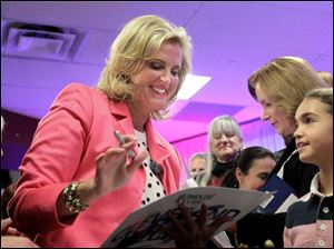 Ann Romney signs autographs after speaking at a victory rally for her husband and presidential candidate Mitt Romney on Thursday in Strongsville.