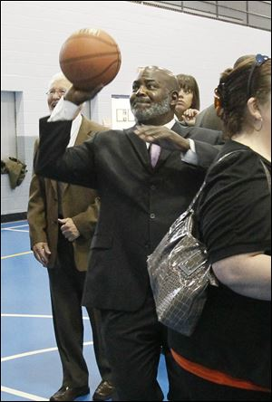 Toledo Mayor Mike Bell takes a shot at the hoop after a press conference announcing that a late-night basketball program is running for six weeks and is focused on providing positive alternative programming for teens and young adults.