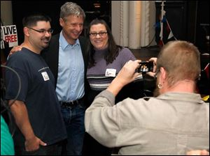 Joe and Angie Kolby, of Toledo, pose with Libertarian presidential candidate Gary Johnson, center, after his speech at the Clazel Theater in Bowling Green, Ohio.
