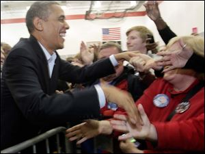 President Obama shakes hands with the overflow crowd in an auxiliary gym after speaking with them before addressing the larger crowd.