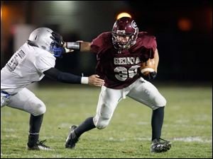 Ryan Espinoza, of the Genoa Comets, dodges a tackle during the first quarter of their Division IV playoff game against the Bishop Ready Knights at Genoa High School.
