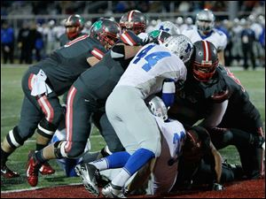 Toledo Central Catholic player DeShone Kizer, 14, right, drives the pile into the end zone as he scores a touchdown during the first quarter against Grafton Midview of their Division II playoff game at Gallagher Stadium in Toledo.