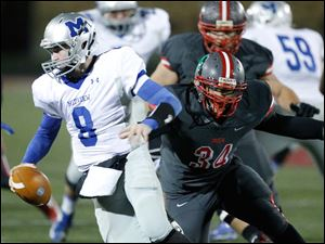 Toledo Central Catholic player Ian Butler, 34, chases Grafton Midview quarterback Cody Callaway, 8, during the first quarter of their Division II playoff game at Gallagher Stadium in Toledo.
