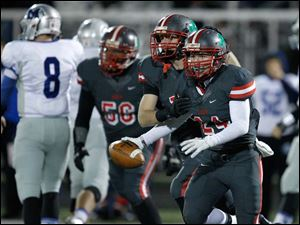 Toledo Central Catholic players Mitchell Cochell, 18, and Derich Weiland, 24, after Weiland intercepted a Grafton Midview pass during the first quarter of their Division II playoff game at Gallagher Stadium in Toledo.