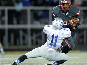 Toledo Central Catholic player Tejuan James, 27, is tackled by Grafton Midview player Zach Bates, 11, after intercepting a pass during the second quarter of their Division II playoff game at Gallagher Stadium in Toledo.